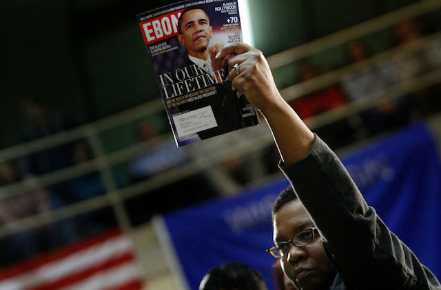 "Black person in dark top holds copy of Ebony high in their left hand. The cover features Barack Obama and reads ""In our lifetime."""
