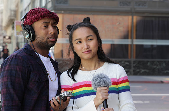 Nyge Turner and Merk Nguyen. Young Black man wearing black headphones and holding a tape recorder. He's wearing a red hat, checkered shirt, white t-shirt  standing next to young Asian American woman holding a microphone. She has long dark hair.