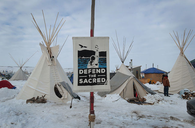 "White teepees in the snow with a protest sign that reads ""Defend the Sacred"" on Standing Rock Reservation"