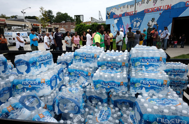 Pallets of water with a line of people standing behind them in Newark, New Jersey at a bottled water distribution center