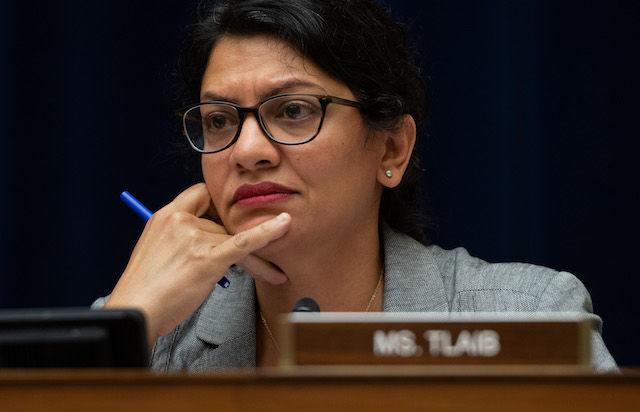 Rashida Tlaib. A brown woman wearing glasses sits at a desk at a House hearing
