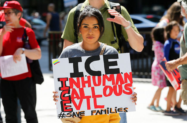 "Woman with dark hair holds protest sign against ICE that reads, ""ICE: Inhuman, callous, evil."""