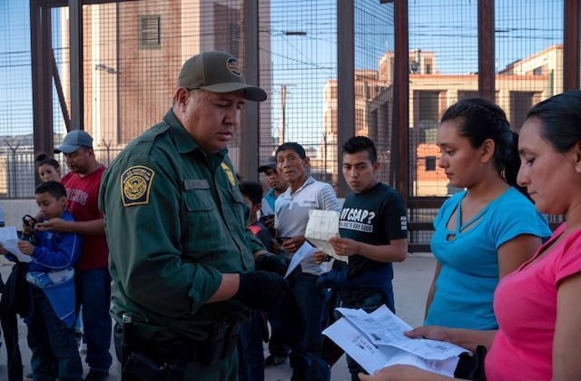 Two women with dark hair have their paperwork checks by a US Customs and Border Protection agent.