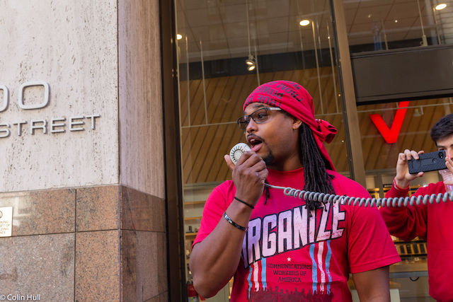 Martin Hopkins. A Black man with dredlocks, wearing a red Communications Workers of America t-shirt, addresses a group of protesters.