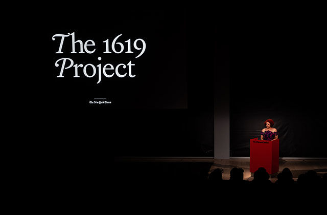 The 1619 Project. Dark stage with Black woman standing at red podium.