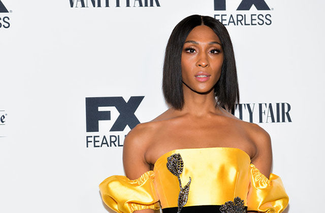 Mj Rodriguez. Latinx woman wearing yellow embellished dress with straight dark dark chin-length hair.