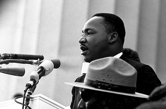 Martin Luther King, Jr. Black and white photo of Black man in front of microphone.