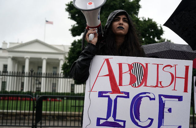 "Latinx person with dark hair and blue lipstick wears black raincoat and holds a white megaphone and sign that reads ""Abolish ICE."""