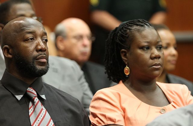 Close-up of a black man and black woman with somber expressions on their faces.