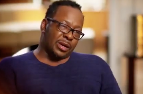 Bobby Brown in blue sweater, black glasses