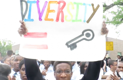 Uniformed high school students, white sign with multicolored lettering