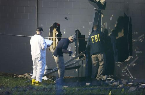 """Three FBI investigators by damage site at Pulse, two in navy jackets with yellow """"FBI"""" lettering"""
