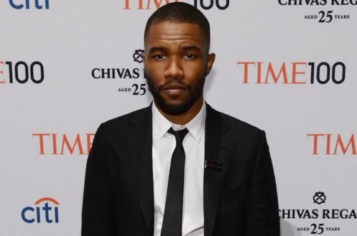 Frank Ocean in black suit with white shirt and black tie