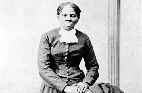 Black woman wearing black button down top with white collar, photo is in black and white