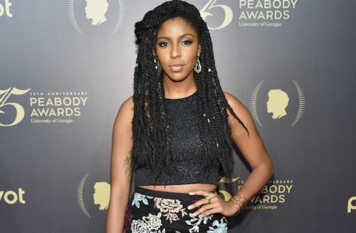Jessica Williams in black top and floral-print skirt