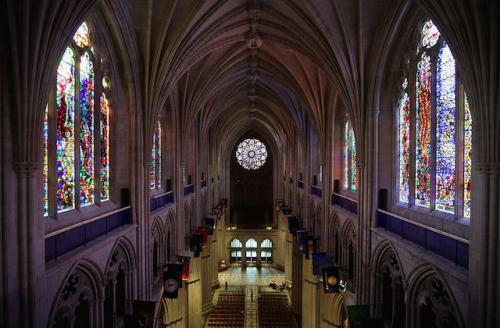 Interior of a large cathedral with high, arched ceilings; stained glass windows line the walls