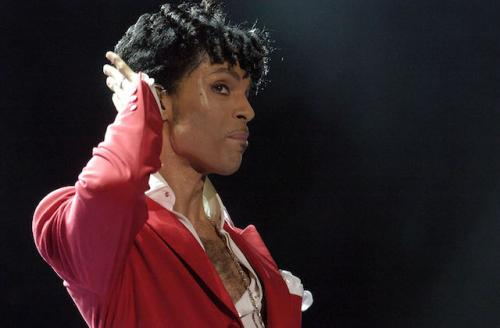 Prince in red jacket and white shirt, in front of black background