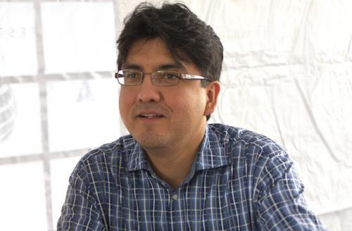 Sherman Alexie in blue and white plaid shirt, white background