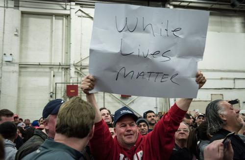 A White man in a red sweatshirt holds up a white sign with black lettering.
