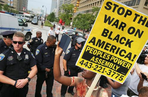 Police officers stand in front of a crowd of protestors holdling signs