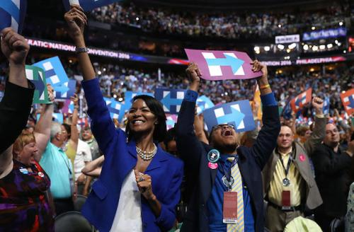 Black man and woman cheer while holding signs in support of Hillary Clinton