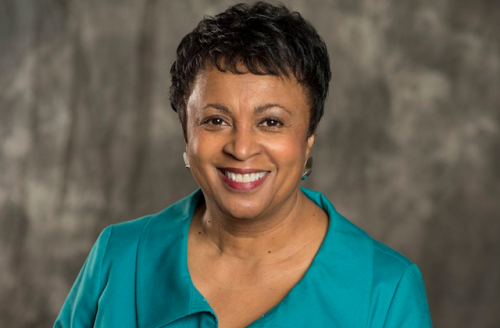 Carla Hayden in turquoise shirt with brown-gray background