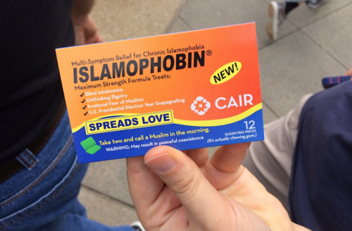 """Orange """"Islamophobin"""" container with white text, held by hand against gray background"""