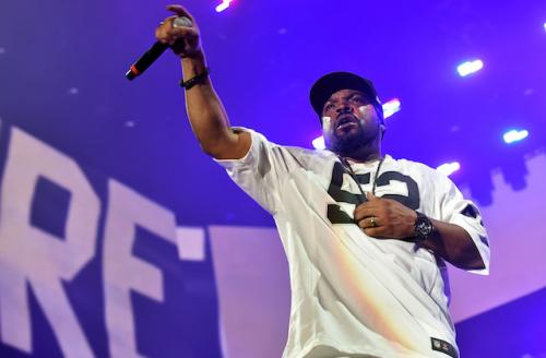 Ice Cube holding black microphone and wearing white jersey with black lettering and black hat
