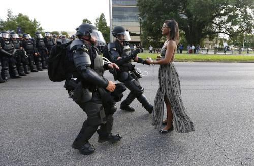 Ieshia Evans standing in blue-green dress in front of black-clad armed police officers