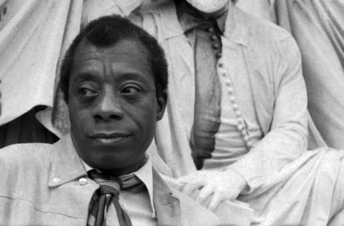 In a black and white photograph, James Baldwin stands in front of a white statue