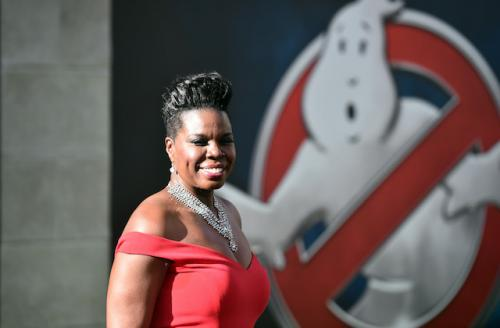 """Leslie Jones in red dress with """"Ghostbusters"""" logo in the back"""