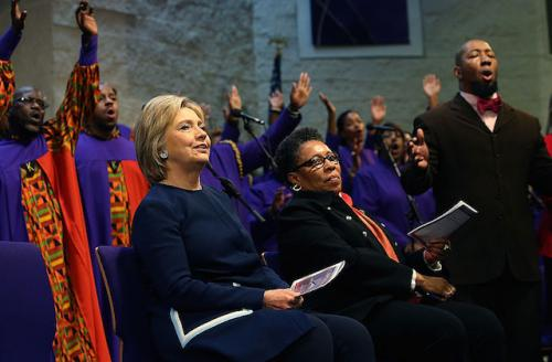 Woman in navy sits beside woman in black and orange in front of the choir stand at a church