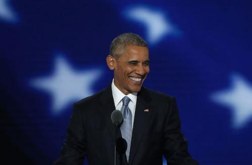 Smiling Black man in black suit, white shirt and blue tie