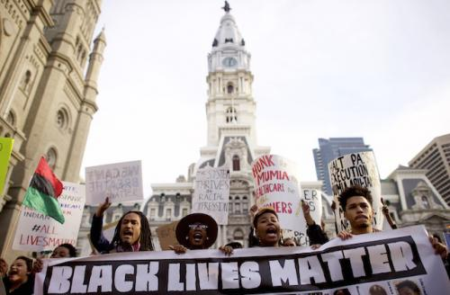 """Black-and-white """"Black Lives Matter"""" sign held by four people, with Philadelphia City Hall in the background"""