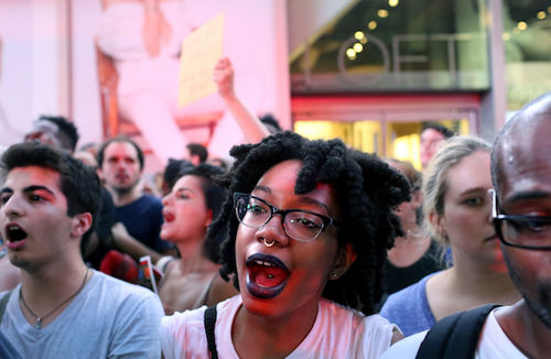 In New York City's Times Square a multiracial crowd protests against the fatal police shootings of Alton Sterling and Philando Castile.