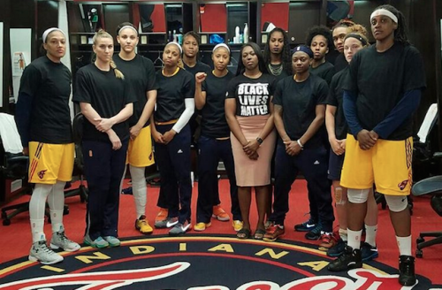 Several Black women wear black shirts, standing in behind the Indiana Fever logo
