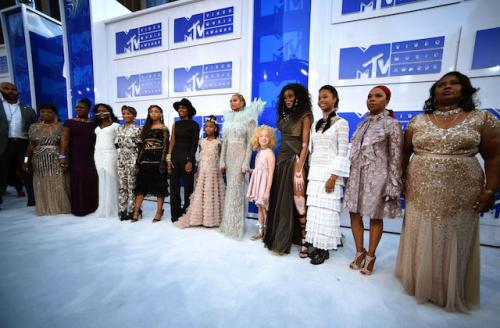 Women, girls and man on white and blue walkway in dresses and outfits of various colors
