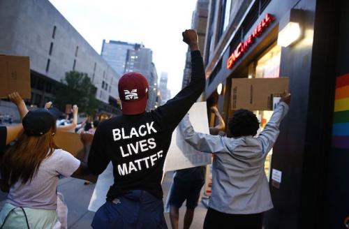 """Black man in black and white """"Black Lives Matter"""" shirt, surrounded by other protesters on a New York City street"""