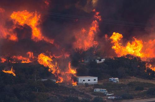Flames sweep through a rural community at the Blue Cut Fire on August 17, 2016, near Wrightwood, California. An unknown number of homes and businesses have burned and more than 82,000 people are under evacuation orders.