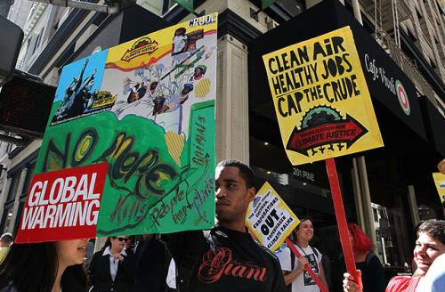 Demonstrators hold signs while marching in the streets as they protest on September 21, 2009, in San Francisco, California.