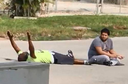 Caretaker Charles Kinsey lays on his back with his hands up.
