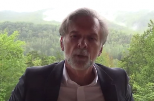 Glen Keith Allen in navy blazer and light blue shirt with green trees in background
