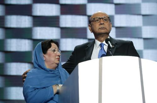 Ghazala Khan in blue hijab next to Khizr Khan in black suit with blue tie and white shirt