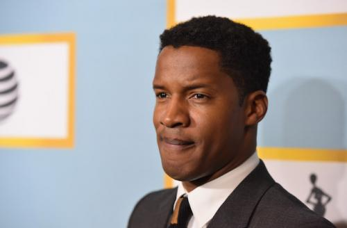 Nate Parker in beige suit and white shirt with dark striped tie