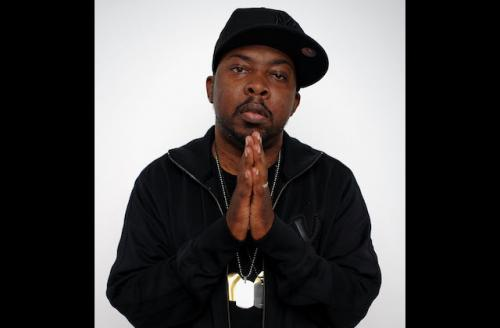Phife Dawg in black outfit, holding hands in prayer formation, with white background