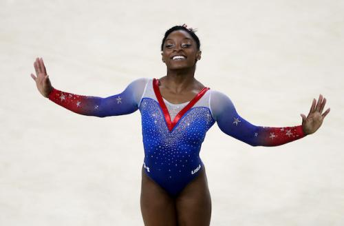 Simone Biles in red, white and blue gymnastics unitard with beige background
