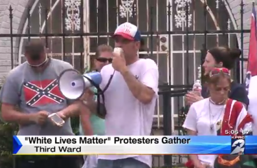 White people wearing Confederate and American flags stand in front of a wrought iron fence