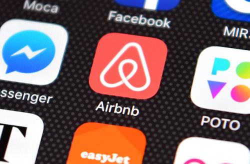 Pink-and-white Airbnb app on black-and-grey iPhone screen surrounded by multi-colored apps