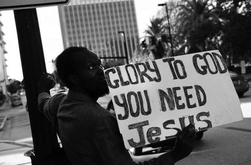 """Black man holds sign that reads: """"Glory to God, you need Jesus."""""""