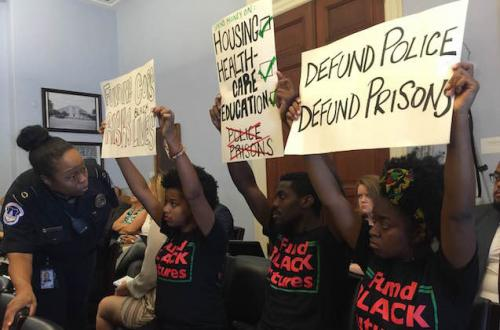 "Young Black activists wearing T-shirts that say ""Build Black futures"" sit in a House Budget Committee meeting holding up signs as a Black woman security guard addresses them."